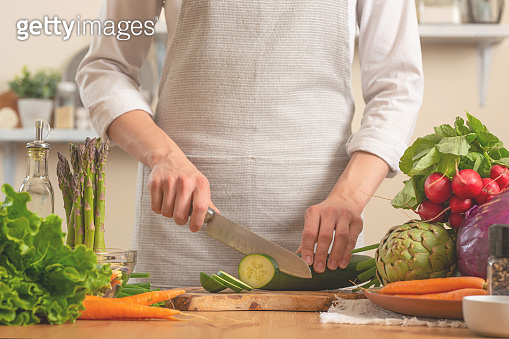 The chef cuts cucumber on a light background. A concept of losing healthy and wholesome food, detox, vegetatry, diet, cooking. Slow food, comfort food, healthy diet, clean eating. Horizontal frame