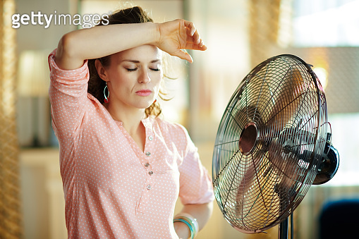 woman exhausted from summer heat while standing in front of fan