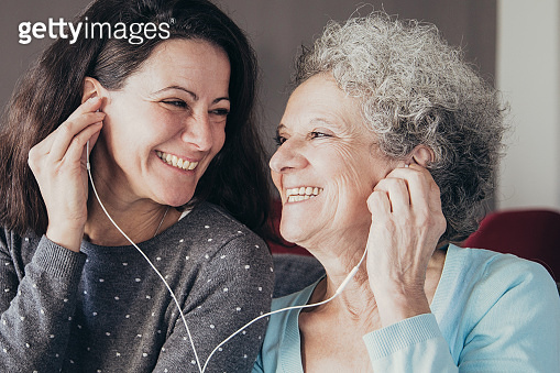Happy senior woman and her daughter listening to music together