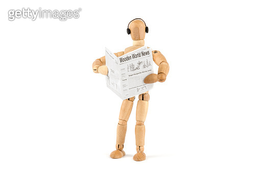 Wooden mannequin reading newspaper and hear nothing else