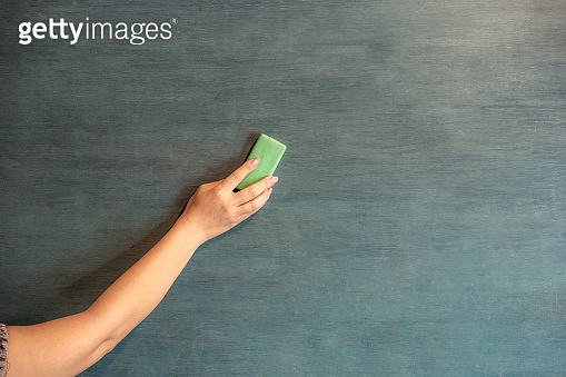 Hands are erasing the blackboard.In the teaching of the use of the blackboard as a medium to teach.