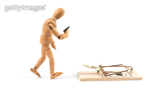 Wooden mannequin looks on mobile phone and pats in mousetrap