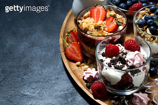 various desserts with berries and cream on dark background, top view