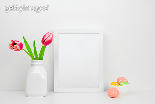 Mock up white frame with Easter Eggs and tulip flowers on a shelf