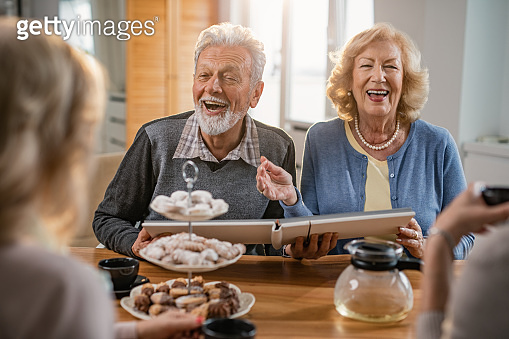 Cheerful mature couple looking at photo album and talking to their friends at home.