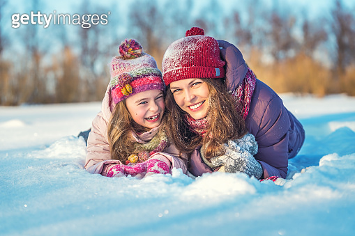 Active mother and daughter playing in winter park