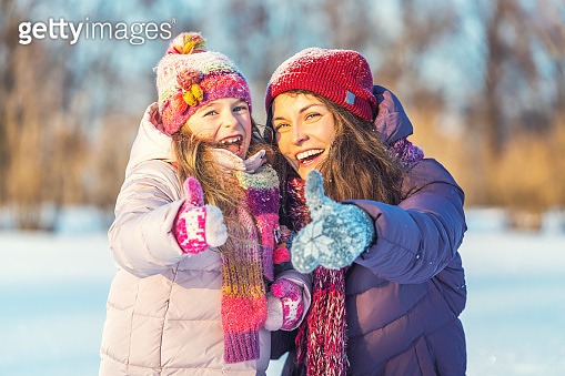 Positive mother and daughter playing in winter park