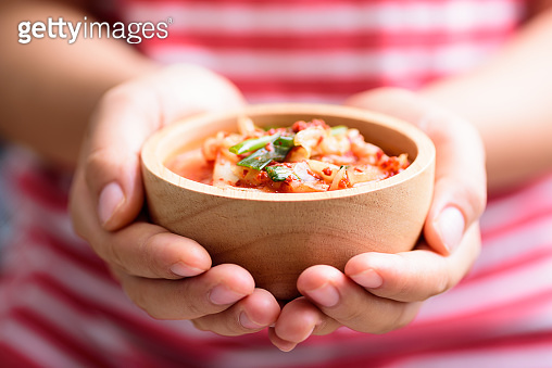 Kimchi cabbage in a bowl holding by hand
