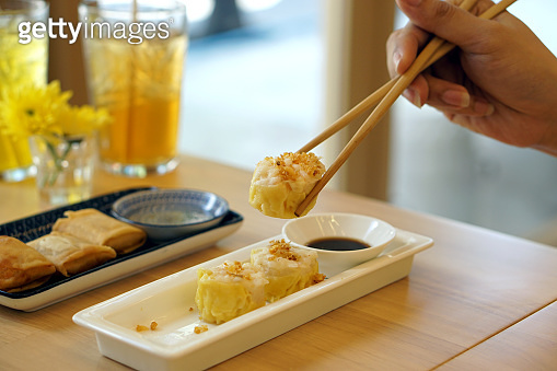 Dim Sum Recipe - Chinese shrimp dumplings topped with fried garlic, served with sour sauce.