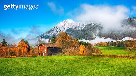 Misty morning view of green meadow near Mitterhofen village
