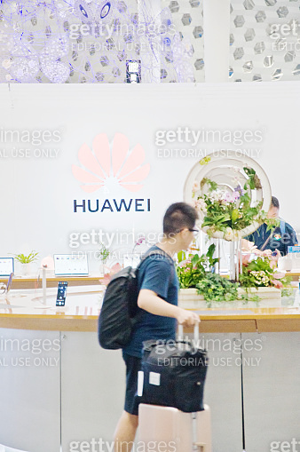 A passenger walking past a Huawei retail shop in Shenzhen Bao'an International Airport (China) terminal