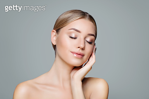 Beautiful smiling woman with clear skin relaxing. Facial treatment, haircare and cosmetology concept