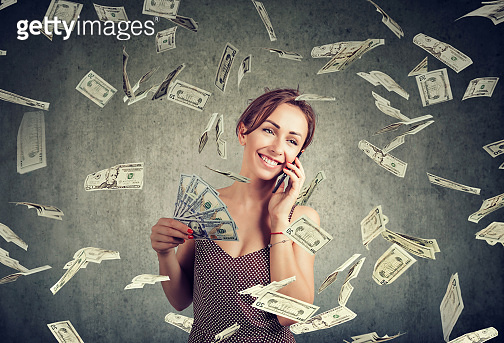 attractive woman talking on a smartphone holding money, cashback under dollar rain