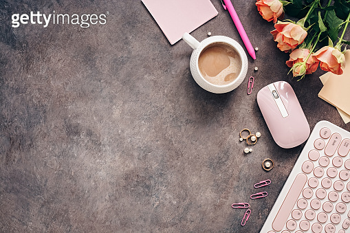 Flat lay female workspace - modern keyboard, mouse, cup of coffee, rose flowers, jewelry and stationery on a dark rustic background. Feminine home office table desk frame. Top view.