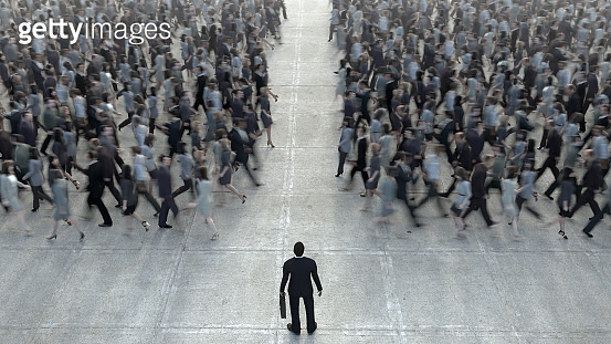 Businessman standing in front of a crowd of competitors