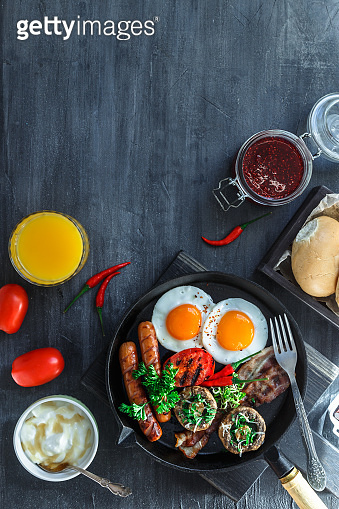 English Breakfast in a pan with fried eggs, sausages, bacon, mushrooms, jam and orange juice on dark stone background copy space, top view flatlay
