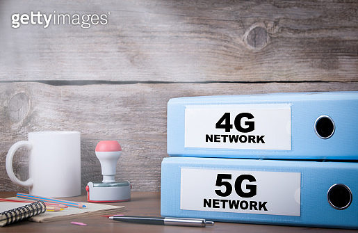 5G and 4G network. Two binders on desk