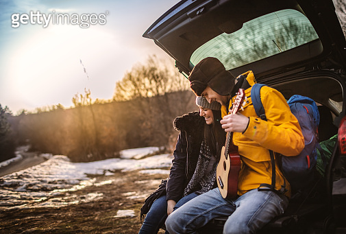 Yong couple with guitar in car trunk