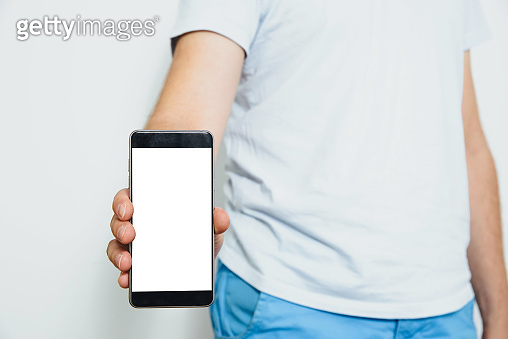 Phone in hand with a blank screen. A man wearing a white T-shirt is holding a phone with a blank display.