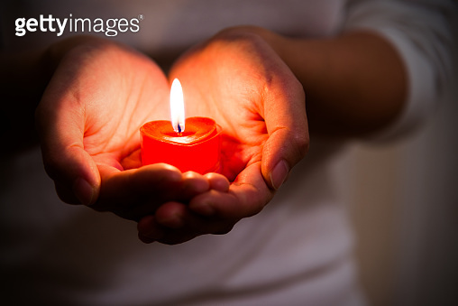 Woman hands holding burning heart-shaped candle