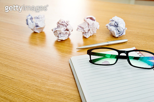 Note pad and crumpled paper balls on wooden table