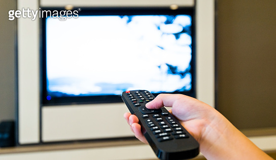 Human hand holding the remote control