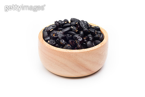 Black beans in wood bowl isolated on white background.
