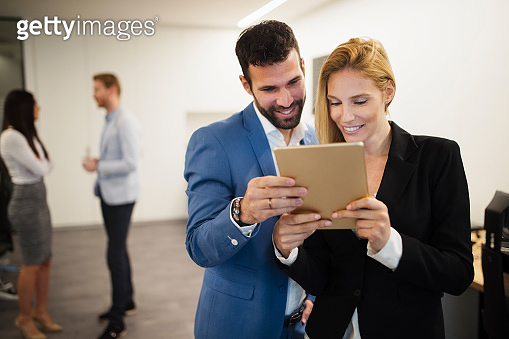 Portrait of attractive business partners using tablet