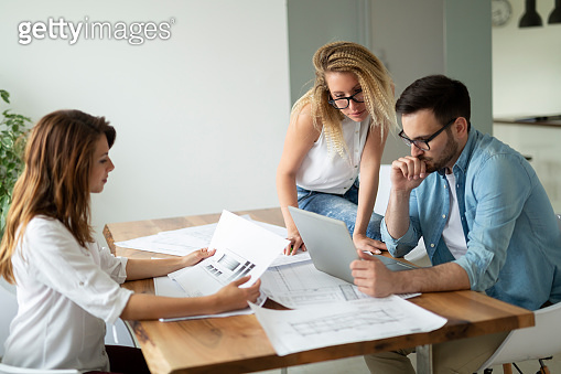 Group of business people working and communicating while sitting at the office desk together