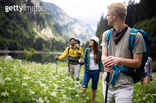 Group of happy young people friends hiking together outdoor