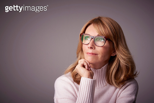 Close-up studio portrait of attractive middle aged woman