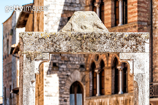 San Gimignano, Italy closeup of ancient stone well in Piazza square in town village in Tuscany during sunny summer