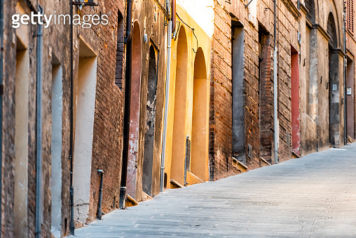 Siena, Italy narrow steep alley street in historic medieval old town village in Tuscany with nobody during summer day and yellow colorful architecture walls doors