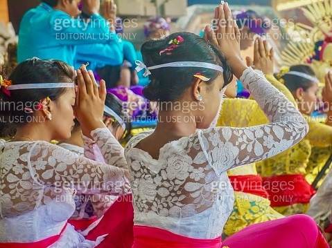 Balinese Hindu worshippers dressed in ceremonial clothing, praying at a festival.