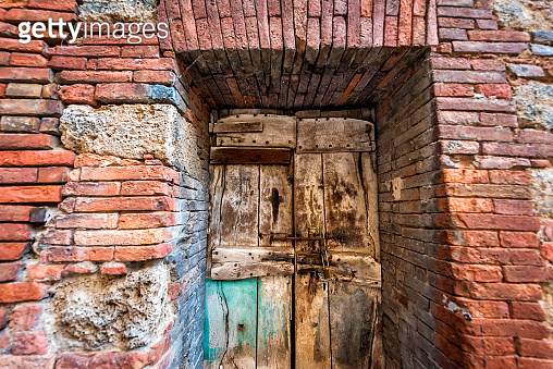 Chiusi, Italy street in small historic medieval town village in Umbria with closeup of colorful red orange stone brick wall and wooden ancient door