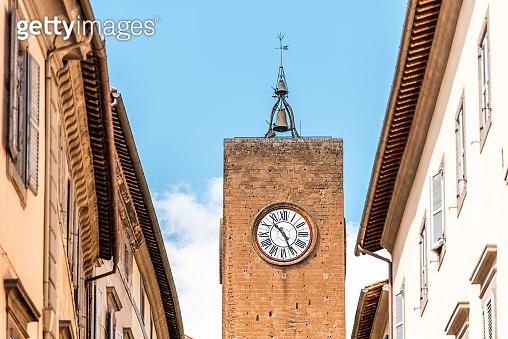Orvieto, Italy Italian outdoor empty street in Umbria historic city town village road narrow alley with orange walls church clock tower closeup