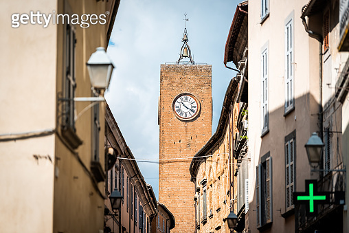 Orvieto, Italy Italian outdoor empty street in Umbria historic city town village road narrow alley with orange walls green pharmacy cross sign and church clock tower