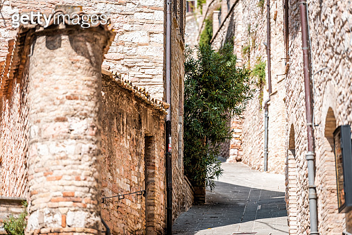 Assisi Umbria Italy empty narrow stone street with nobody on road in small historic medieval town village during summer day architecture