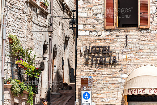 Street in Umbria city town village with nobody and sign for Hotel Italia by narrow alley
