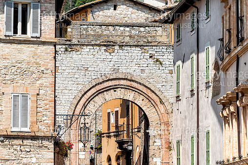 Umbria city with street road arch entrance during sunny summer day in historic St Francis town village