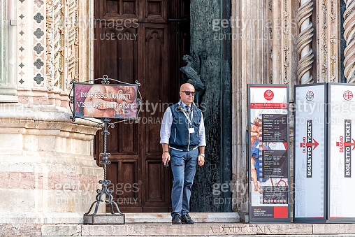 Old town Italian village with man by entrance of church for tickets in famous square Piazza del Duomo by doors