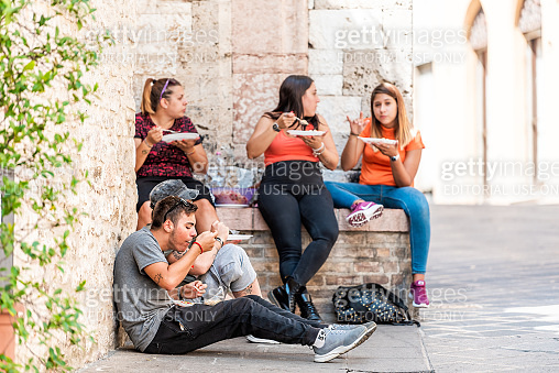 Many young people Italian teenager local tourists eating on street in Umbria city town village