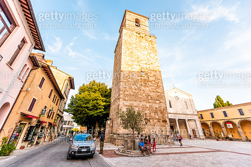 Street square with church tower in small town village in Umbria during day with people and stone architecture