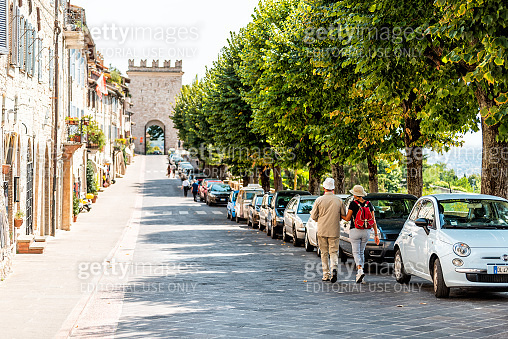 Umbria city with tourists people walking on street road during sunny summer day