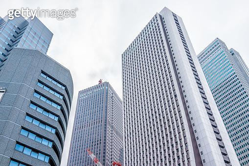 Shinjuku, Tokyo cityscape with low angle view of modern contemporary glass office skyscraper highrise apartment buildings and cloudy sky