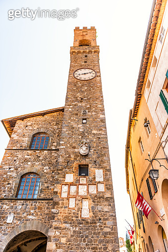 Montalcino, Italy - August 26, 2018: Street in town village in Tuscany during summer day and clock bell tower vertical closeup view