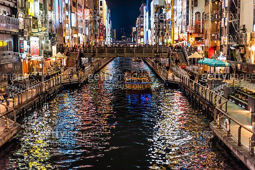 Minami Namba famous street with people on boat in night and illuminated Dotombori river