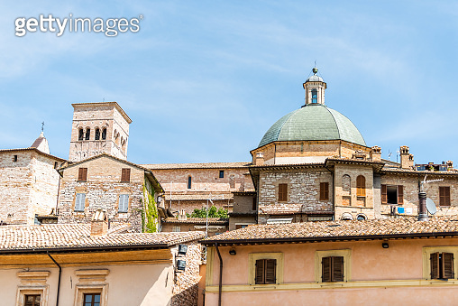 Town or village city of Assisi in Umbria, Italy closeup cityscape view of New Church during sunny summer day and roof buildings