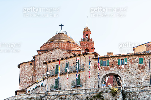 Medieval fortress fort wall in Umbria in sunny summer day cityscape with church tower and people by entrance low angle view