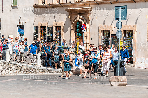 Many people tourists tour group walking on street in Umbria city town village crowded at popular famous attraction